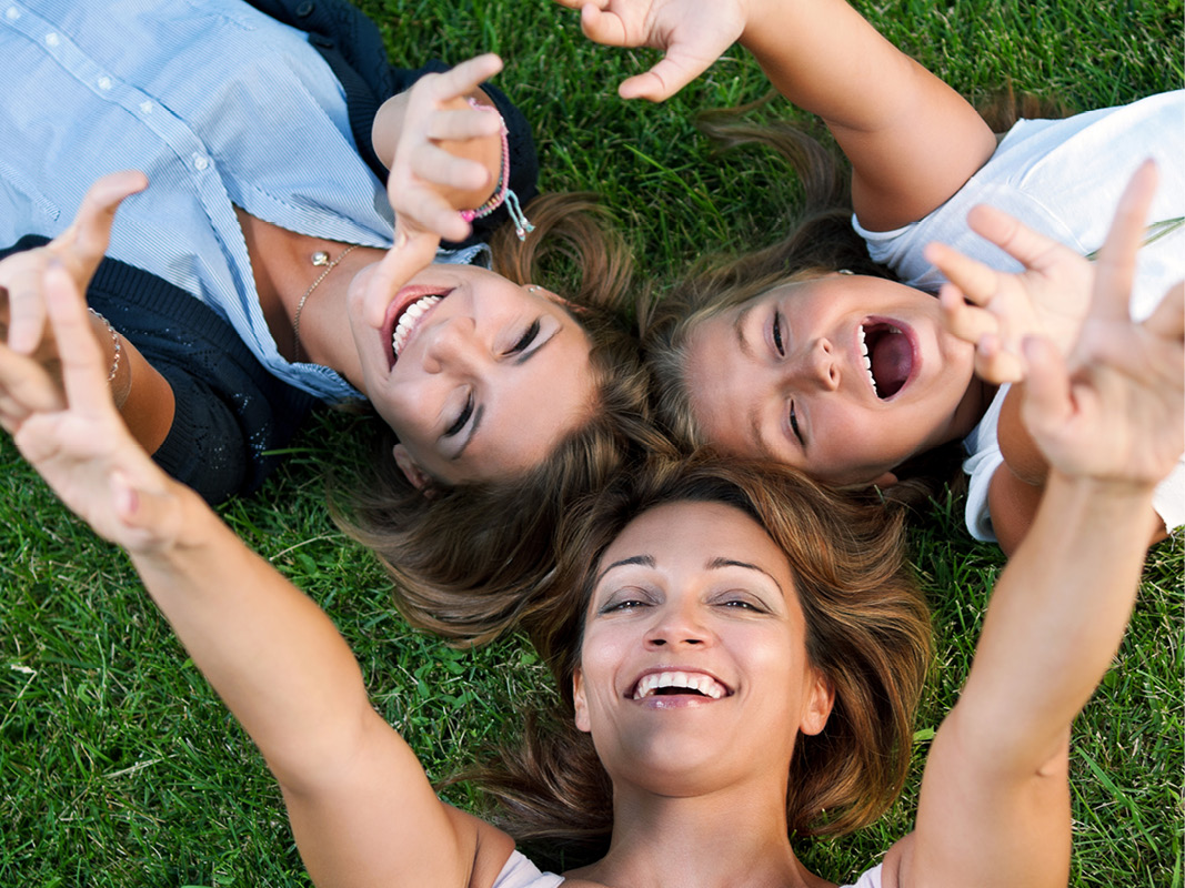 Three women of different ages laying on the ground with their heads together and reaching up