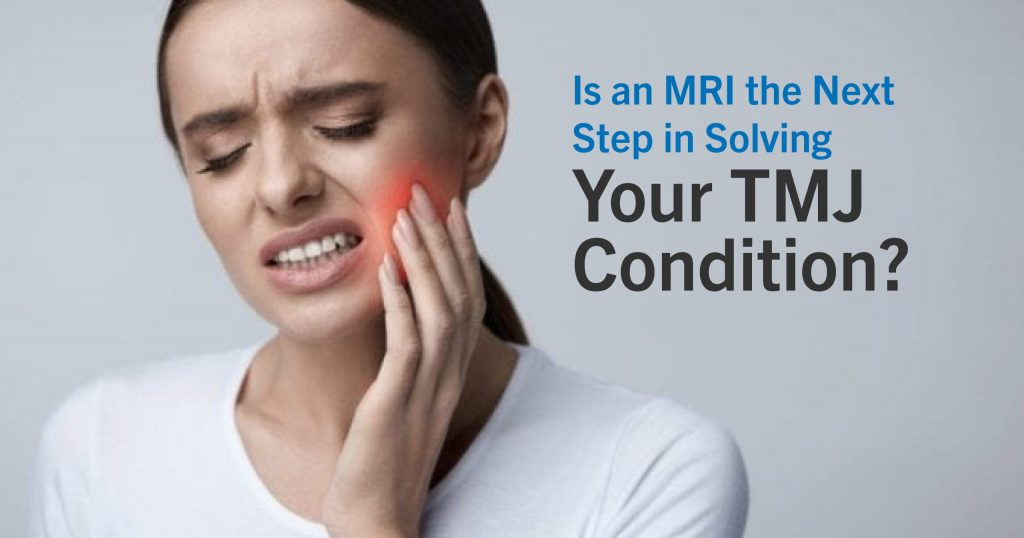Young woman holding her cheek from TMJ pain